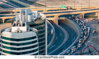 Aerial view of a highway intersection in Dubai, UAE, at sunset with traffic timelapse.