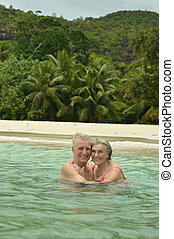 elderly couple swimming at tropical beach - Happy elderly...
