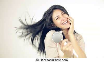 Happy woman playing with long hair blow drying isolated -...