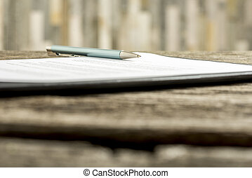 Low angle view of a pen lying on a contract, legal paper or...
