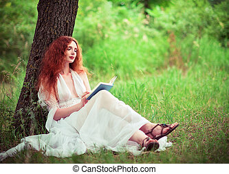 Beautiful ginger woman sitting under tree and reading a book...
