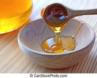Honey - Wooden spoon pouring honey in a wooden bowl