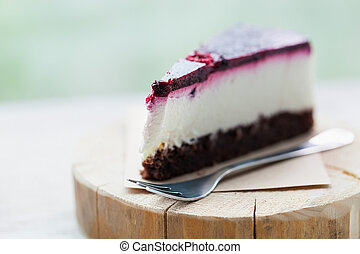 Slice of delicious raspberry cheesecake on wooden plate -...
