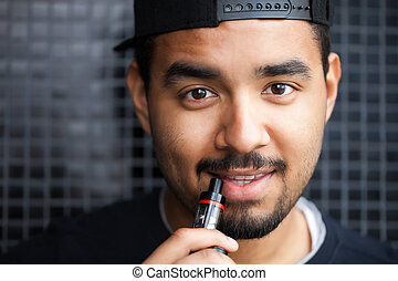 Young black hip hop guy smoking e-cig vaporizer - Portrait...