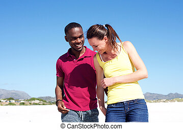 Young couple walking together on the beach