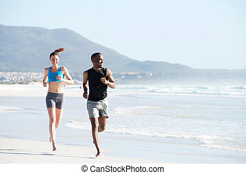 Fit young man and woman running along the beach