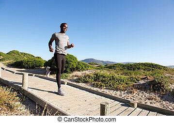 Healthy young african man running on boardwalk at the beach...