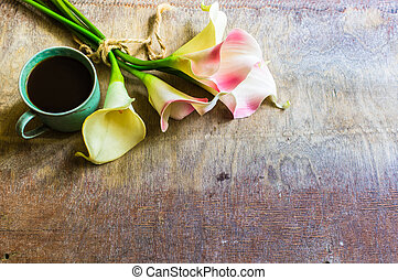 Calla flowers and cup og coffee on rustic table - Cup of...