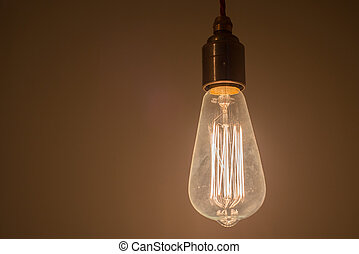 A Lit Up Light Bulb - A lit up incandescent light bulb with...