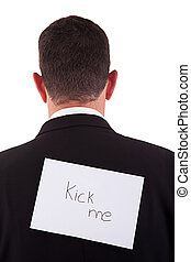 back of businessman, with kick me written in a paper ,...