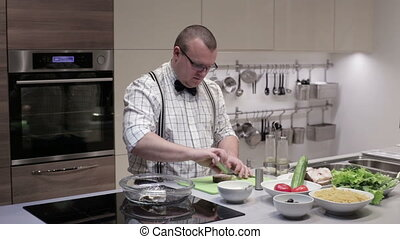 A man prepares fish steaks - A man in a bow tie and...