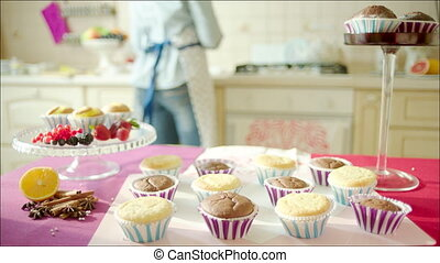 Woman engaged on making muffins - Shot of tasty cup-cakes on...