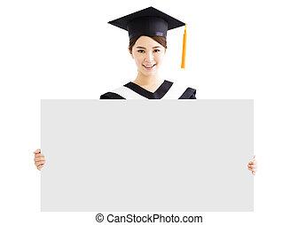 happy female graduate showing copy space on blank board