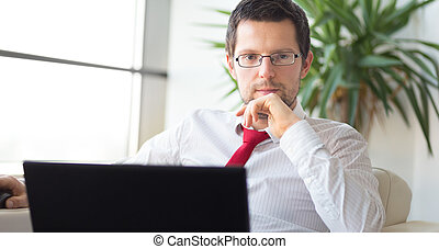 Portrait of businessman working on laptop computer -...