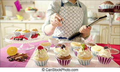 Woman counting ready cup-cakes