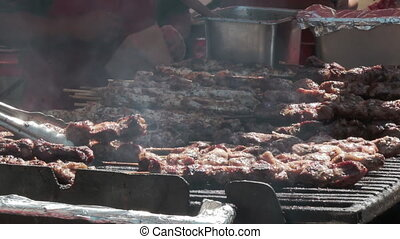 Juicy roasted chicken skewers,made of white meat and bacon, being turned on the bbq