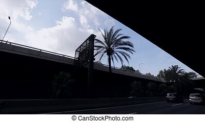 View at silhouette of bridge in city. Summer sunny day. Palm trees. Road with driving cars