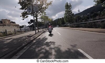 Front view people ride on motorcycle in city. Many green trees. Summer sunny day. Traveling world