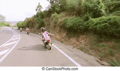Back side of people ride on motorcycle on road at mountains. Many green trees. Summer sunny day.