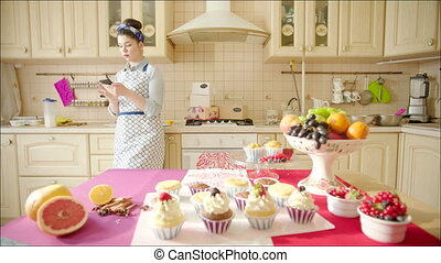 Woman using smartphone in the kitchen