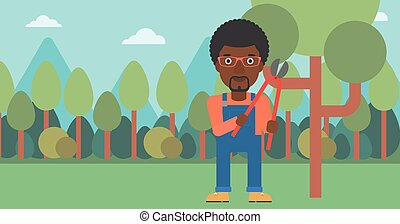 Farmer with pruner in garden - An african-american man...