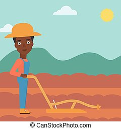 Farmer on the field with plough - An african-american woman...