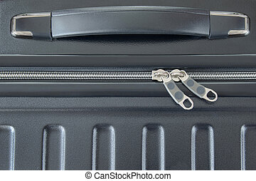 Top view of silver zipper of hard shelled suitcase, new and...