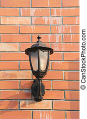 Black Lantern mounted on brown brick wall.