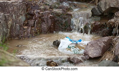 The thrown bottle floats in the river. environmental...