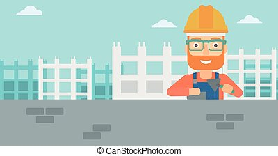 Bricklayer with spatula and brick. - A hipster bricklayer...