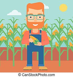 Farmer holding corn - A hipster man with the beard holding a...