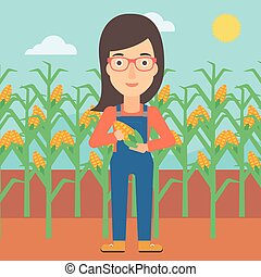 Farmer holding corn. - A woman with holding a corn cob on...