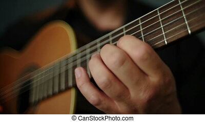 A man plays the guitar chords changing fingers