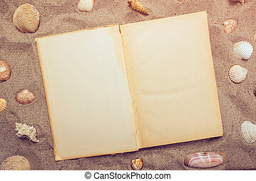 Top view of open book on sandy beach, blank vintage pages as...