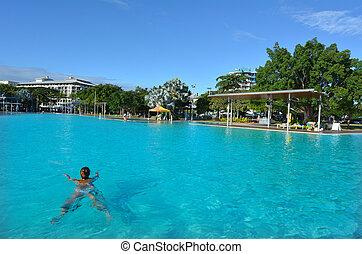 Woman swim in Cairns Esplanade Swimming Lagoon in Queensland...