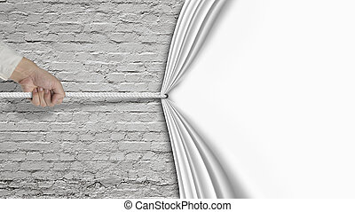 Hand pulling down white curtain covering old brick wall...