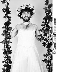 Bearded man in a woman's wedding dress, clinging to the vine. grimacing and funny. on his head a wreath of flowers. funny bearded bride. black and white.