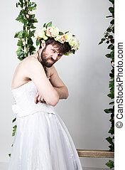 Bearded man in a woman's wedding dress, folded his arms, he is dissatisfied. on his head a wreath of flowers. funny bearded bride