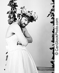 Bearded man in a woman's wedding dress, folded his arms, he is dissatisfied. on his head a wreath of flowers. funny bearded bride. black and white