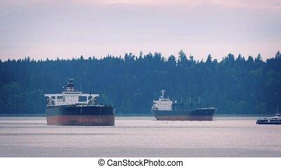 Passenger Ferry Passes Between Ship - Ferry travels between...