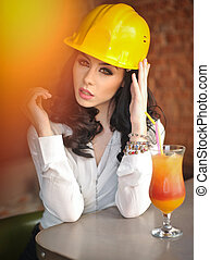 Beautiful woman civil engineer with yellow helmet taking a...