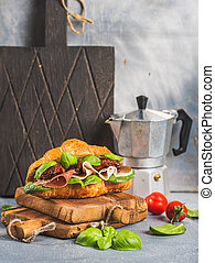 Croissant sandwich with smoked meat Prosciutto di Parma, sun...