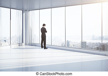 Thoughtful man in room - Thoughtful businessman standing in...