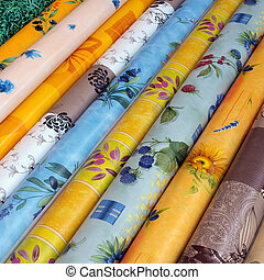 Rolls of textiles at the market - a display of colorful...
