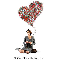 Sewing love - Woman sews to crochet a big heart