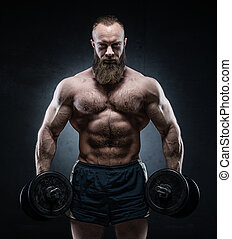 Bearded Muscular bodybuilder posing with heavy dumbbells on...