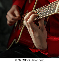 Closeup portrait of a man in a red shirt, playing on a red...