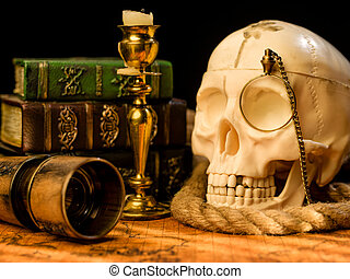 Old vintage candlestick, skull and spyglass on ancient world...