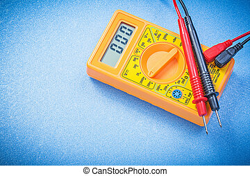 Electrical digital multimeter on blue background directly...