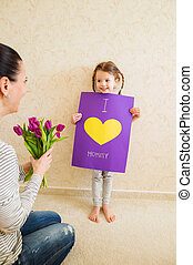 Mothers day, girl giving flowers and card to her mum